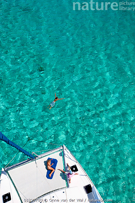People sunbathing and swimming from a catamaran in the Grenadines, Caribbean. February 2010.  ,  ABOARD,ANCHORED,CARIBBEAN,CRUISING,DECKS ,HIGH ANGLE SHOT,HOLIDAYS,LIFESTYLE,PEOPLE,RELAXATION,SAILING BOATS,SWIMMING,TROPICAL,TURQUOISE,VERTICAL,WEST INDIES,YACHTS,CONCEPTS ,BOATS ,core collection xtwox,BOAT-PARTS  ,  Onne van der Wal