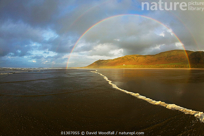 Incoming tide and double rainbow caused by precipitation and wave spray, with house on the Rhosilli down coastline. West-facing beach in Rhosilli Bay, Gower Peninsular, Area of Outstanding Natural Beauty, Swansea, West Glamorgan, Wales. December 2009.  ,  ATMOSPHERIC,COASTS,ESTUARIES,EUROPE,LANDSCAPES,RAINBOWS,TIDAL,TIDES,UK,WATER,WEATHER,United Kingdom,WALES  ,  David Woodfall