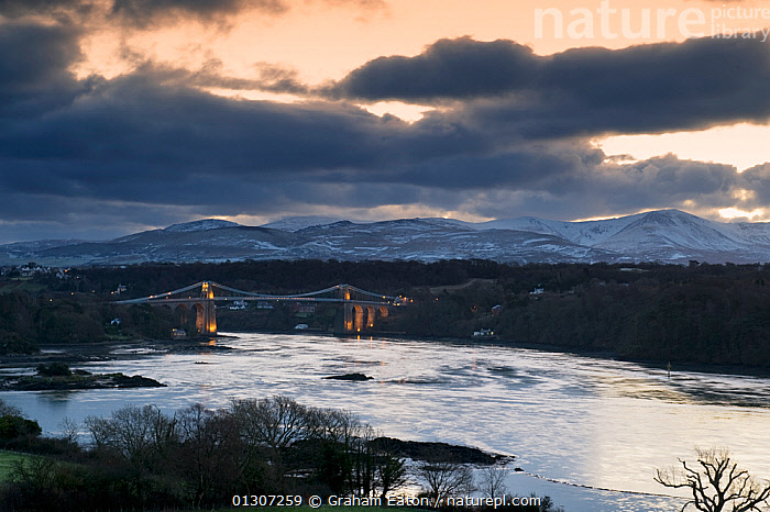 Menai Suspension Bridge, view at dawn from Anglesey towards Snowdonia, Wales, January 2010.  ,  BRIDGES,BUILDINGS,CALM,CLOUDS,DAWN,EUROPE,LANDSCAPES,LIGHTS,MOUNTAINS,RIVERS,SNOW,TRAFFIC,UK,WALES,WINTER,Weather,United Kingdom  ,  Graham Eaton