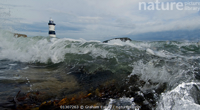 A low angle view of Penmon lighthouse with waves crashing towards the camera, Anglesey, Wales, October 2009.  ,  EUROPE,LIGHTHOUSES,SURF,UK,WALES,WATER,WAVES,WINTER,BUILDINGS ,United Kingdom,core collection xtwox  ,  Graham Eaton