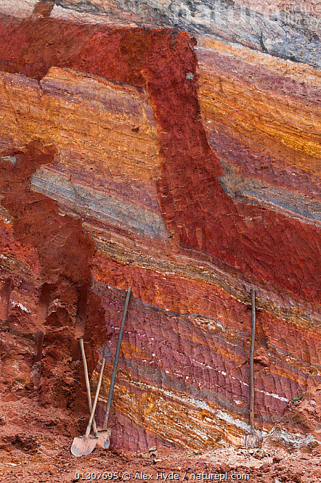 Clay deposits visible as distinct layers, exposed after roadside excavation, with workers' tools included for scale, Andasibe-Mantadia National Park, Madagascar.  ,  CLIFFS,GEOLOGY,MADAGASCAR,NP,RESERVE,ROCK FORMATIONS,STRIATIONS,VERTICAL,National Park  ,  Alex Hyde