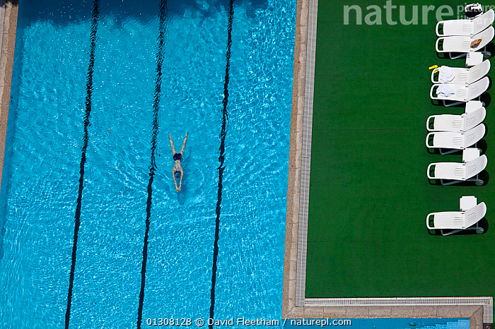 Aerial view of woman swimming in pool in Guangzhou, China., AERIALS,ASIA,CONCEPTS,HIGH ANGLE SHOT,HOLIDAYS,LEISURE,PEOPLE,RELAXATION,RIPPLES,SUN LOUNGERS,SWIMMING,SWIMMING POOLS ,WOMAN, David Fleetham