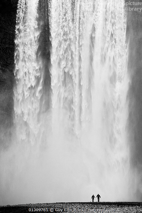 Two people silhouetted in front of Skogafoss waterfall in southern Iceland, June 2009  ,  ATMOSPHERIC,awe,catalogue3,DRAMATIC,EUROPE,force of nature,ICELAND,imposing,in front of,LANDSCAPES,nature,outdoors,PEOPLE,power,SCALE,seacliff,SILHOUETTES,Skogafoss waterfall,Southern Iceland,STANDING,tourist destination,Travel,travel destination,two people,WATER,waterfall,WATERFALLS,waterspray,CONCEPTS,core collection xtwox,,Journeyman,Travel,Wanderlust,,Wonder,Spectacular,  ,  Guy Edwardes