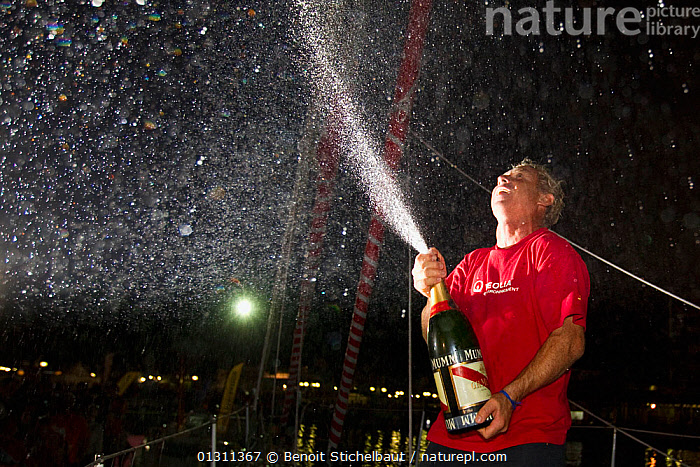 """Monocoque 60 """"Veolia Environment"""" skipper Roland Jourdain celebrating arrival in Guadeloupe as winner of Route du Rhum IMOCA Class. November 2010. Editorial use only., BOATS,CARIBBEAN,CELEBRATIONS,CENTRAL AMERICA,CHAMPAGNE,COASTS,CONCEPTS,CREWS,GUADELOUPE,MAN,NIGHT,PEOPLE,RACES,RUM RACE,SAILING BOATS,SKIPPER,SPLASHES,SUCCESS,WEST INDIES,WINNER,WINNERS,YACHTS,core collection xtwox, Benoit Stichelbaut"""