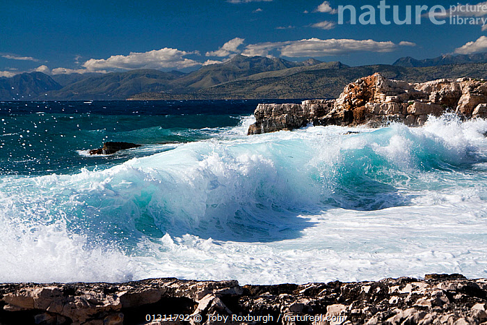 Waves breaking onto rocky shore, northeast coast of Corfu, with the Albanian coast in the background, Corfu, Greece, June 2010., BREAKING,COASTS,CORFU,EUROPE,GREECE,HEAVY SEAS,LANDSCAPES,MEDITERRANEAN,MOUNTAINS,ROCKS,WAVES,core collection xtwox, Toby Roxburgh