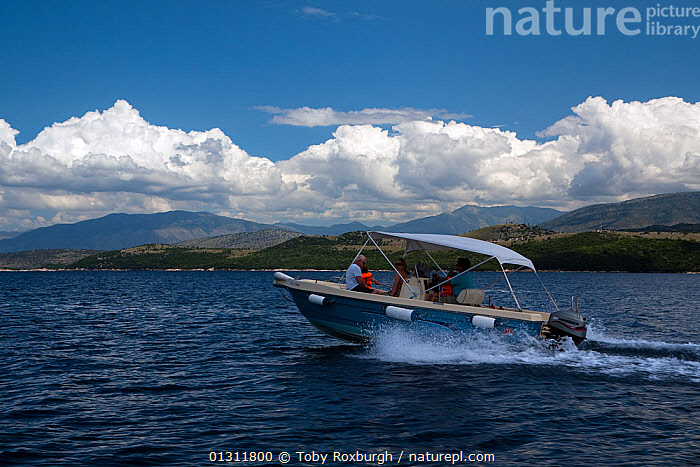 Motorboat with family aboard cruising off the north-east coast of Corfu, with the coast of Albania in the background, Corfu, Greece, June 2010. Model released., BOATS,COASTS,CRUISING,EUROPE,GREECE,HOLIDAYS,LANDSCAPES,MEDITERRANEAN,MOTORBOATS,PEOPLE,PROFILE,SMALL,Concepts,SIZE, Toby Roxburgh