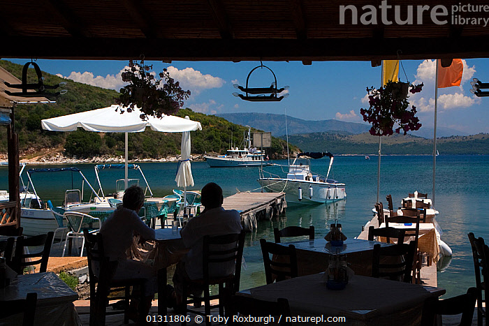 Couple sitting in a beachside restaurant in San Stefanos Bay, with the mountains of Albania visible in the distance. Corfu, Greece, June 2010., BOATS,BUILDINGS,COASTS,CORFU,COUPLES,CRUISING,ESCAPISM,EUROPE,GREECE,HOLIDAYS,JETTIES,LEISURE,MEAL,MEDITERRANEAN,MOORED,MOTORBOATS,PEOPLE,RESTAURANT,RESTAURANTS,CONCEPTS, Toby Roxburgh