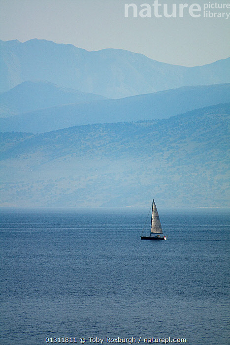 Yacht sailing in the straits between northern Corfu, Greece, and Albania, June 2010., BOATS,COASTS,CORFU,CRUISING,EUROPE,GREECE,MAINSAILS,MEDITERRANEAN,MIST,PROFILE,SAILING BOATS,VERTICAL,YACHTS,WEATHER, Toby Roxburgh
