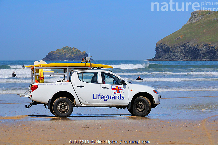 RNLI surf lifeguard driving rescue car on Polzeath beach, with surfers in waves behind. Cornwall, UK, April 2010., BEACHES,COASTS,EUROPE,LANDSCAPES,LEISURE,LIFEGUARDS,PEOPLE,SEA,SEARCH RESCUE,SPORTS,SURF,UK,VEHICLES,WATERSPORTS,WAVES,United Kingdom,core collection xtwox, Nick Upton