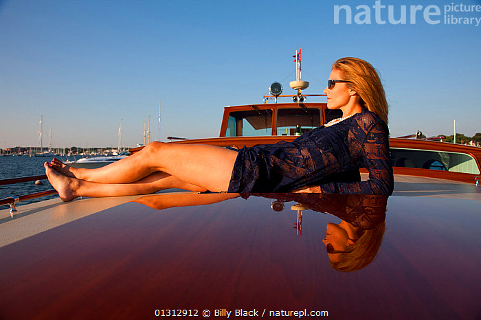 """Woman relaxing on board luxury motorboat """"Aphrodite"""". Newport, Rhode Island, USA, July 2010. Model and Property released.  ,  ABOARD,BOATS,CLOTHING,COASTS,CONCEPTS,CRUISING,GLAMOUR,LEISURE,LIFESTYLE,LUXURY,MOTORBOATS,NORTH AMERICA,PEOPLE,REFLECTIONS,SUNGLASSES,USA,WOMAN,WOODEN,core collection xtwox  ,  Billy Black"""