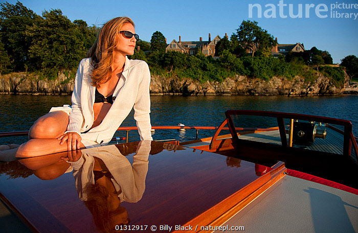 """Woman relaxing on board luxury motorboat """"Aphrodite"""". Newport, Rhode Island, USA, July 2010. Model and Property released.  ,  ABOARD,BOATS,COASTS,CRUISING,ESCAPISM,GLAMOUR,LEISURE,LIFESTYLE,MOTORBOATS,NORTH AMERICA,PEOPLE,REFLECTIONS,SUNGLASSES,SWIMWEAR,USA,WOMAN,WOODEN,CONCEPTS,CLOTHING  ,  Billy Black"""