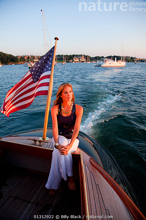 """Woman relaxing on stern of luxury motorboat """"Aphrodite"""". Newport, Rhode Island, USA, July 2010. Model and Property released.  ,  ABOARD,BOATS,COASTS,COCKPITS,CONCEPTS,CRUISING,ENSIGNS,FLAGS,GLAMOUR,LEISURE,LIFESTYLE,MOTORBOATS,NORTH AMERICA,PEOPLE,TEAK,USA,VERTICAL,WAKE,WOMAN,WOODEN,BOAT-PARTS  ,  Billy Black"""