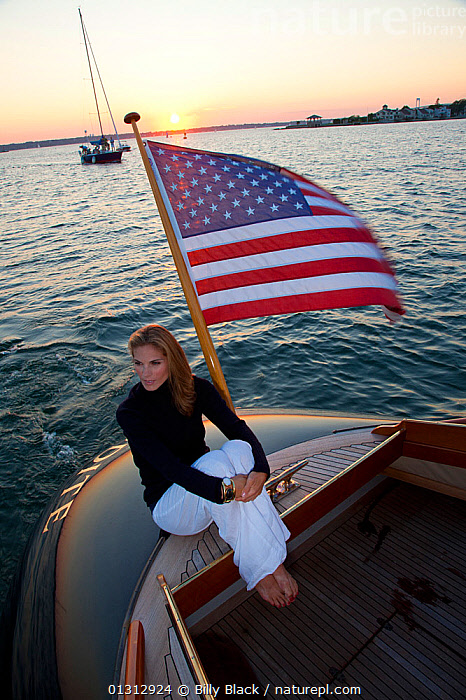 """Woman relaxing on stern of luxury motorboat """"Aphrodite"""". Newport, Rhode Island, USA, July 2010. Model and Property released.  ,  ABOARD,BOATS,COASTS,COCKPITS,CONCEPTS,CRUISING,DUSK,ENSIGNS,FLAGS,GLAMOUR,HIGH ANGLE SHOT,LEISURE,LIFESTYLE,MOTORBOATS,NORTH AMERICA,PEOPLE,SUNSET,TEAK,USA,VERTICAL,WAKE,WOMAN,WOODEN,BOAT-PARTS  ,  Billy Black"""
