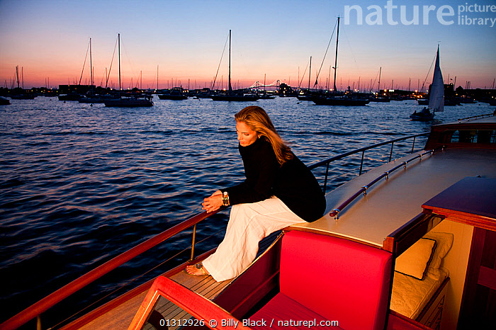 """Woman relaxing on stern of luxury motorboat """"Aphrodite"""" in the evening. Newport, Rhode Island, USA, July 2010. Model and Property released.  ,  ABOARD,BOATS,COASTS,COCKPITS,CONCEPTS,CRUISING,DUSK,GLAMOUR,HARBOURS,LEISURE,LIFESTYLE,LUXURY,MOORED,MOTORBOATS,NIGHT,NORTH AMERICA,PEOPLE,SILHOUETTES,TEAK,USA,WOMAN,WOODEN,BOAT-PARTS,core collection xtwox  ,  Billy Black"""