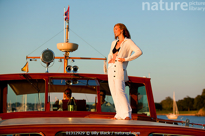 """Woman relaxing on board luxury motorboat """"Aphrodite"""". Newport, Rhode Island, USA, July 2010. Model and Property released.  ,  ABOARD,BOATS,carefree,CLOTHING,COASTS,concepts,CREWS,CRUISING,GLAMOUR,LEISURE,LIFESTYLE,MEN,MOTORBOATS,NORTH AMERICA,PEOPLE,SMILING,SWIMWEAR,USA,WOMAN,WOODEN,core collection xtwox  ,  Billy Black"""