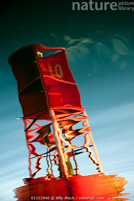 Red channel marker reflected in water. Northeast Harbour, Maine, August 2010.  ,  ABSTRACT,ARTY SHOTS,BUOYS,NORTH AMERICA,REFLECTIONS,RIPPLES,SURFACE,USA,VERTICAL,WATER  ,  Billy Black