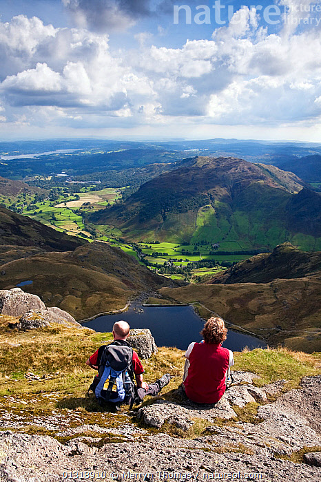 Couple looking out over Stickle Tarn and Great Langdale valley, from Pavey Ark. Lake District, Cumbria, England. September 2010.  ,  COUPLES,ENGLAND,EUROPE,HIGH ANGLE SHOT,HIKING,LAKES,LANDSCAPES,LEISURE,MOUNTAINS,PEOPLE,UK,VERTICAL,WALKERS,WALKING,United Kingdom,core collection xtwox  ,  Merryn Thomas