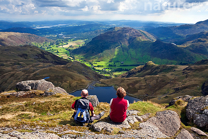 Couple looking out over Stickle Tarn and Great Langdale valley, from Pavey Ark. Lake District, Cumbria, England. September 2010.  ,  COUPLES,ENGLAND,EUROPE,HIGH ANGLE SHOT,HIKING,LAKES,LANDSCAPES,LEISURE,MOUNTAINS,PEOPLE,UK,WALKERS,WALKING,United Kingdom,core collection xtwox  ,  Merryn Thomas