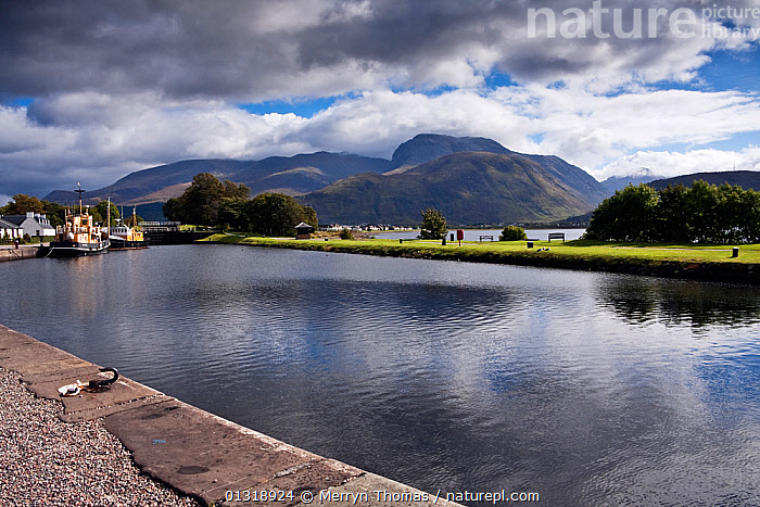 Start of the Caledonian Canal at Corpach, with Ben Nevis beyond. Fort William, Highlands, Scotland. September 2010.  ,  BOATS,BUILDINGS,CANALS,EUROPE,LANDSCAPES,MOORED,MOUNTAINS,REFLECTIONS,SCOTLAND,UK,WORKING BOATS,United Kingdom  ,  Merryn Thomas