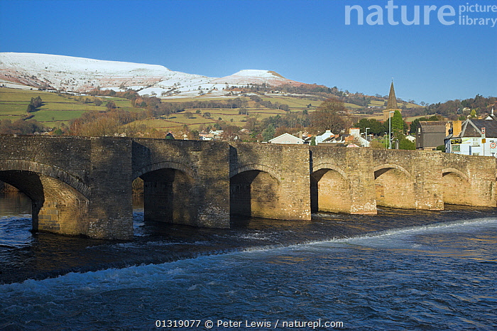 The 17th century bridge at Crickhowell, Powys, with snow covered hills beyond. Brecon Beacons National Park, Wales, January 2010.  ,  BRIDGES,BUILDINGS,COUNTRYSIDE,EUROPE,hills,LANDSCAPES,RIVERS,SNOW,UK,VILLAGES,WATER,WALES,United Kingdom  ,  Peter Lewis