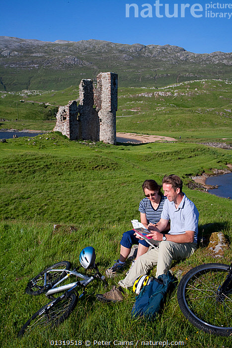 Couple relaxing during bike ride in front of Ardvreck Castle. Loch Assynt, Sutherland, Scotland, July Model released  ,  ADULT,BIKES,BUILDINGS,CASTLES,CYCLING,EUROPE,LANDSCAPES,LEISURE,MAN,PEOPLE,RUINS,SCOTLAND,TWO,UK,VERTICAL,WOMAN,United Kingdom  ,  Peter Cairns
