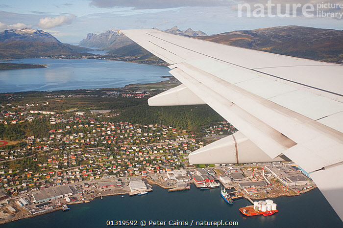 Aerial view over Tromso from an aeroplane window, Norway, September 2009.  ,  AERIALS,BUILDINGS,CITIES,CITYSCAPES,COASTS,DOCKS ,EUROPE,HIGHLANDS,INDUSTRY,LANDSCAPES,MOUNTAINS,NORWAY,SCANDINAVIA,WINGS  ,  Peter Cairns