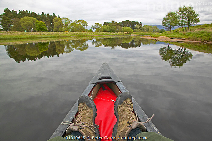 The River Spey seen from a canoe, including the photographer's feet. Cairngorms National Park, Scotland, June 2006.  ,  CANOEING,COUNTRYSIDE,EUROPE,LANDSCAPES,OUTDOORS,PEOPLE,REFLECTIONS,RIVERS,SCOTLAND,TOURISM,TREES,UK,WATER,PLANTS,United Kingdom  ,  Peter Cairns