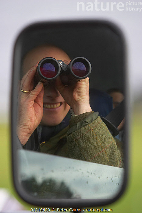 Man reflected in a wing mirror, looking from the window of a car with binoculars. Islay, Scotland, March.  ,  BIRD WATCHING,EUROPE,OUTDOORS,PEOPLE,SCOTLAND,UK,VEHICLES,VERTICAL,United Kingdom , Inner Hebrides  ,  Peter Cairns