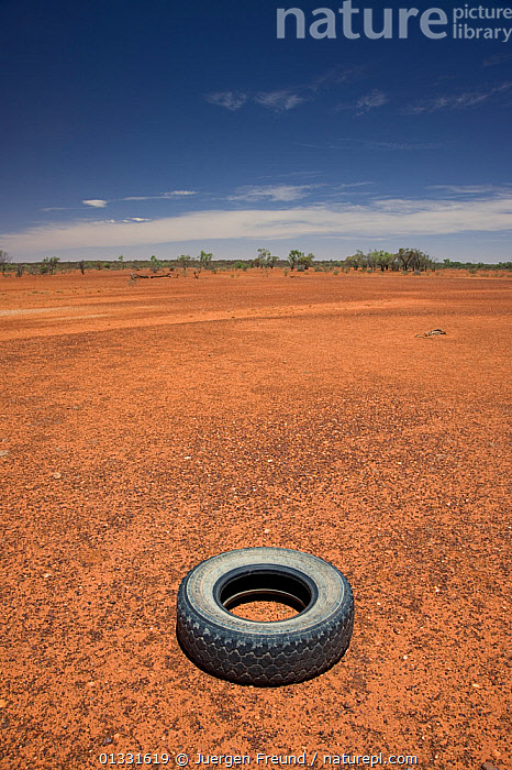 Discarded truck tyre in the dry red desert of the Australian centre by the highway between Mt. Isa and Boulia. Queensland, Australia, February 2008  ,  arid,AUSTRALASIA,AUSTRALIA,bare,barren,DESERTS,Earth,EMPTY,environment,hostile,LANDSCAPES,lonely,Nobody,outback,RED,VERTICAL  ,  Jurgen Freund