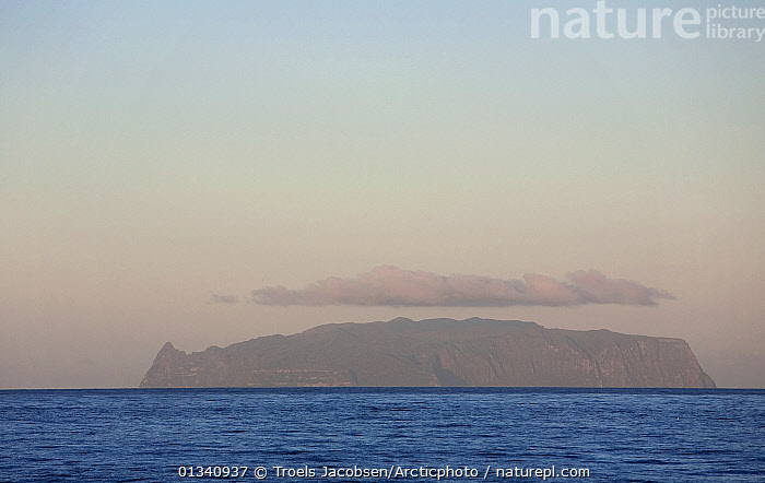 Inaccessible Island on the horizon topped with clouds. UNESCO World Heritage site and part of the Tristan da Cunha Group of South Atlantic Islands, March 2007., ATLANTIC ISLANDS,ATLANTIC OCEAN,ISLANDS,LANDSCAPES,OCEANS,SEAS,SEASCAPES,TRISTAN DA CUNHA,WATER, Troels Jacobsen/Arcticphoto