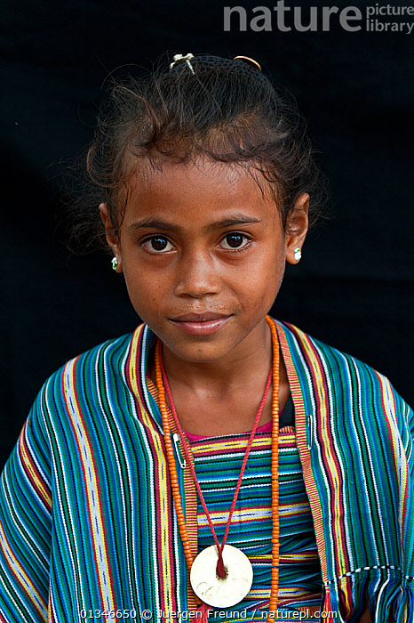 Portrait of East Timorese girl in traditional clothing, Maubara, East Timor, August 2010  ,  Asian,catalogue4G,child,CHILDREN,coral triangle,East Timor,front view,girl,half length,INDO PACIFIC,local people,looking at camera,Maubara,one girl only,one person,PEOPLE,portrait,PORTRAITS,SMILING,SOUTH EAST ASIA,STANDING,striped pattern,traditional dress,VERTICAL,WWF  ,  Jurgen Freund