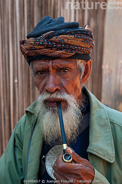 Portrait of elderly East Timorese man in traditional clothing, Maubara, East Timor, August 2010.  ,  ASIAN,CORAL TRIANGLE,ELDERLY,INDO PACIFIC,MAN,PEOPLE,PIPE,PORTRAITS,SMOKING,SOUTH EAST ASIA,VERTICAL,  ,  Jurgen Freund
