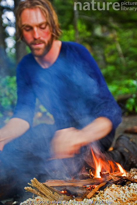 A hiker building a fire at his campsite. The West Coast Trail, Pacific Rim National Park, Vancouver Island, Canada, September 2010. Model released., British Columbia,Campfire,CAMPING,CANADA,catalogue4,Caucasian,Fires,focus on foreground,hiker,looking down,MAN,mid adult,NORTH AMERICA,NP,one man only,one person,outdoors,Pacific Rim ,PEOPLE,RESERVE,SITTING,smoke,Vancouver,Vancouver Island,VERTICAL,West Coast Trail,west canada,Selective focus,National Park, Matthew Maran