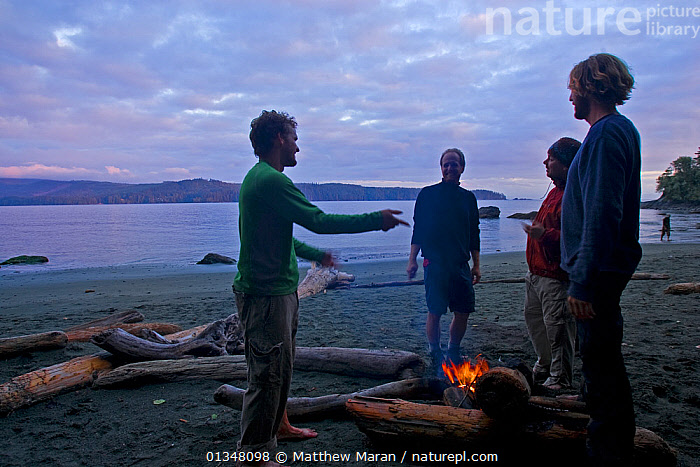 Hikers talking as they warm themselves by a campfire on a beach. The West Coast Trail, Pacific Rim National Park, Vancouver Island, Canada, September 2010. Models released.  ,  beach,BEACHES,British Columbia,Campfire,CAMPING,camps,CANADA,catalogue4,ENJOYMENT,four people,FRIENDSHIP,full length,hand gesture,hiker,hiking,LANDSCAPES,log,MEN,men only,mid adult,NORTH AMERICA,NP,Pacific Rim ,PEOPLE,RESERVE,SMILING,STANDING,talking,TOURISM,Vancouver,Vancouver Island,warmth,West Coast Trail,west canada,Concepts,National Park  ,  Matthew Maran