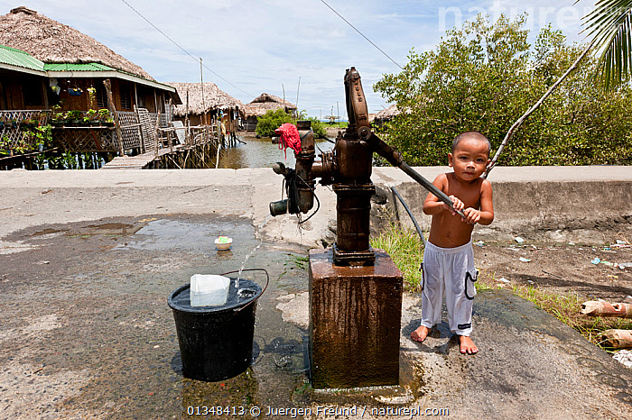 A Filipino toddler pumping water out of the community water pump for his bath. Donsol, Philippines, June 2009., ASIA,BATHING,BUILDINGS,CHILDREN,CORAL TRIANGLE,CULTURES,INDO PACIFIC,PEOPLE,SOUTH EAST ASIA,TODDLERS,VILLAGES,WATER,,SOUTH-EAST-ASIA, Jurgen Freund