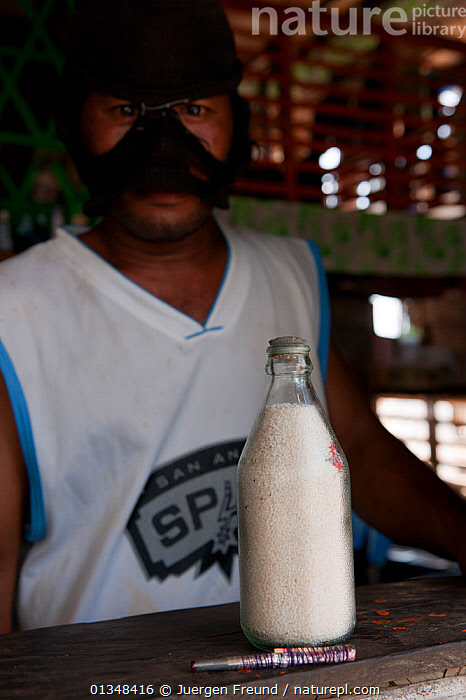 Man preparing a homemade explosive for fishing. The bomb is made by filling a glass bottle with potassium or ammonium nitrate, kerosine and rocks. It is thrown onto a reef with schooling fish and indiscrimately kills everything in the water. Palawan, Phillipines, April 2009 . NOT AVAILABLE FOR MAGAZINE USE IN GERMAN-SPEAKING COUNTRIES UNTIL 1ST JULY 2013., ASIA,BLASTING,BOMBS,CORAL TRIANGLE,CULTURES,DANGEROUS,DYNAMITE,DYNAMITING,ENVIRONMENTAL,FISHING,HABITAT DESTRUCTION,ILLEGAL,INDOORS,INDO PACIFIC,MAN,PEOPLE,SOUTH EAST ASIA,VERTICAL,, Jurgen Freund