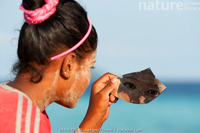 A young Bajau woman with burak (face makeup) looking at herself in a scrap of mirror. Burak is a paste made from pounded rice and tumeric and also serves as a natural sunblock. Wearing burak signifies the young lady is single and available for marriage. Sibuan Island, Malaysia, June 2009 . NOT AVAILABLE FOR MAGAZINE USE IN GERMAN-SPEAKING COUNTRIES UNTIL 1ST JULY 2013., ADORNMENT,ASIA,CORAL TRIANGLE,COSMETICS,CULTURES,EYES,INDO PACIFIC,ISLANDS,MAKE UP,MIRRORS,PEOPLE,REFLECTIONS,SOUTH EAST ASIA,TRADITIONAL,WOMEN,,YOUNG, Jurgen Freund