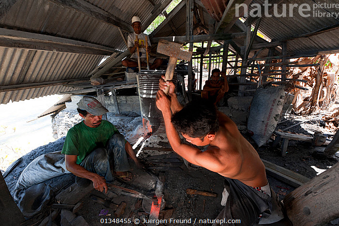 Famous Binongko tukangbesi (blacksmiths) forging machetes from spring steel. Wakatobi, Sulawesi, Indonesia, November 2009.  ,  ACTION,ASIA,BLACKSMITH,CORAL TRIANGLE,CULTURES,FORGE,HAMMER,HAMMERING,HITTING,INDOORS,INDO PACIFIC,KNIVES,MAKING,MEN,PEOPLE,SOUTH EAST ASIA,TRADITIONAL,WORKING,  ,  Jurgen Freund