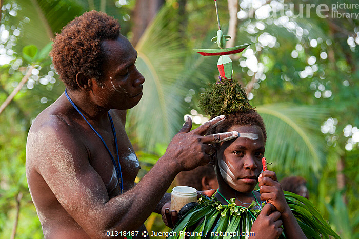 Man applying lime paste to the face of a boy for a sing-sing performance, known as laklakau in the Tigak language, by Enuk villagers.  Kavieng, Papua New Guinea, June 2010.  ,  ASIA,BOYS,CELEBRATIONS,CORAL TRIANGLE,CULTURES,DECORATION,INDO PACIFIC,MAKE UP,MEN,PAINT,PAINTING,PEOPLE,PERFORMANCES,RITUALS,SOUTH EAST ASIA,TRADITIONAL,TROPICAL,  ,  Jurgen Freund