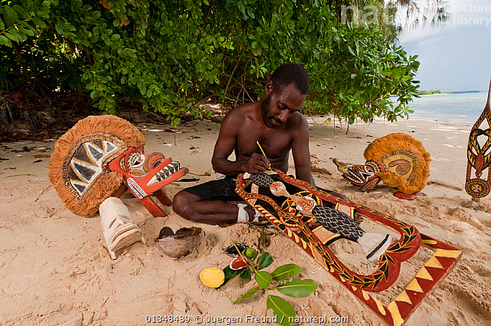 Papua New Guinean artist carving Malagan wooden sculptures, the ceremonial art of New Ireland's living culture, from the soft, abundant Saba tree wood. He uses four natural pigments for paint.  Kavieng, Papua New Guinea, June 2010., ART,ARTISTS,ASIA,BEACHES,CARVING,CORAL TRIANGLE,CULTURES,INDO PACIFIC,MASKS,MEN,PEOPLE,SCULPTURES,SOUTH EAST ASIA,TRADITIONAL,WOODEN,WORKING,, Jurgen Freund