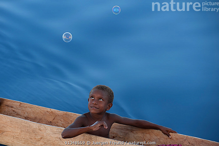 Young Papua New Guinean islander enjoying bubbles blown towards him by tourists. Papua New Guinea, June 2010., ASIA,BOYS,CANOES,CHILDREN,CORAL TRIANGLE,CULTURES,INDO PACIFIC,PLAYING,SMILING,SOUTH EAST ASIA,,YOUNG, Jurgen Freund