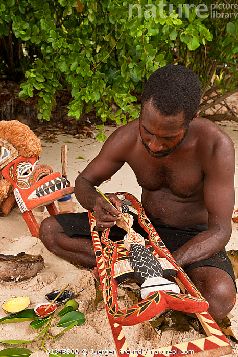 Papua New Guinean artist carving Malagan wooden sculptures, the ceremonial art of New Ireland's living culture, from the soft, abundant Saba tree wood. He uses four natural pigments for paint. Kavieng, Papua New Guinea, June 2010., ART,ARTISTS,BEACHES,CARVING,CORAL TRIANGLE,CULTURES,INDO PACIFIC,MASKS,MEN,PEOPLE,SCULPTURES,SOUTH EAST ASIA,TRADITIONAL,VERTICAL,WOODEN,WORKING,, Jurgen Freund