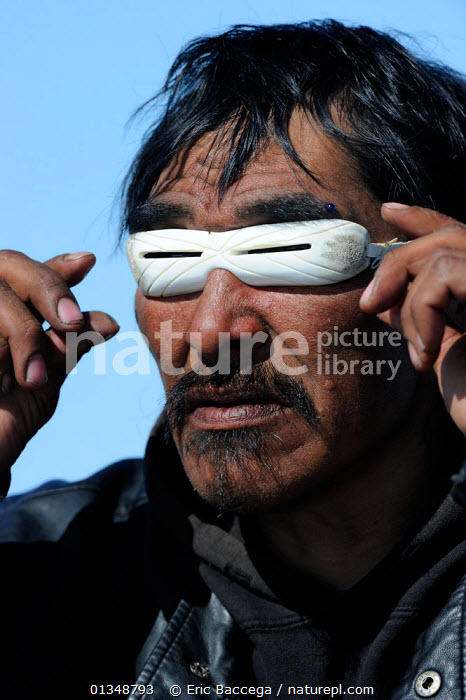 Portrait of Inuit man with traditional sunglasses made from whale bone. Igloolik, Foxe Basin, Nunavut, Canada, April 2009. Model released., ARCTIC,CANADA,catalogue4,close up,craft,craftwork,eyesight,eyewear,FACES,Foxe Basin,full frame,glasses,head and shoulders,HEADS,Igloolik,inuit,local people,looking,MAN,mid adult,NORTH AMERICA,Nunavut,one man only,one person,outdoors,PEOPLE,portrait,PORTRAITS,protection,SUN,sunglasses,TRADITIONAL,TRIBES,VERTICAL,whale bone, Eric Baccega