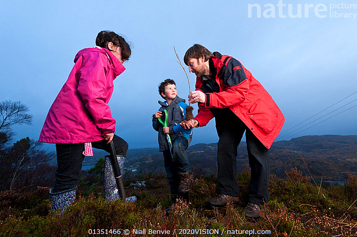 Children from Lochinver primary school being shown how to plant trees on moorland at Culag Wood, Sutherland, Highlands, Scotland, UK, January 2011. Did you know? One tree can remove up to one tonne of CO2 in its lifetime.  ,  2020VISION,ASSYNT,BOY,CAUCASIAN,CHILDREN,COMMUNITY,CONSERVATION,COOPERATION,EDUCATION,ENERGY,EUROPE,picday,FEMALE,GIRL,IFTE NB 013965,MALE,MOORLANDS,MOUNTAINS,NBE_03_21011_0008,OUTDOORS,PEOPLE,PLANTING,REFORESTATION,REWILDING,SAPLINGS,SCOTLAND,TEACHING,THREE,TREES,UK,UPLANDS,WINTER,WOODLANDS,WORKING,YOUNG,PLANTS,United Kingdom  ,  Niall Benvie / 2020VISION