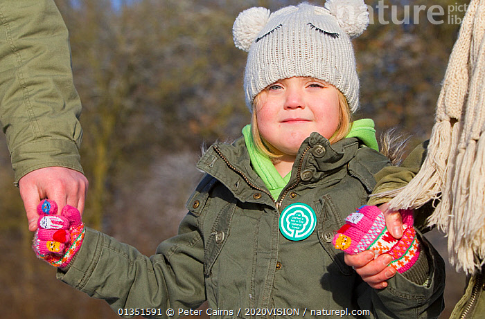 Young girl wearing a badge for The National Forest, with the volunteers planting sapling trees as part of The National Forest's planting day, Moira, Derbyshire, UK, November 2010  ,  2020VISION,child,CHILDREN,COLD,CONSERVATION,ENGLAND,EUROPE,FAMILIES,FORESTS,HANDS,Midlands,outdoors,pca_1_210411_46,PEOPLE,PORTRAITS,snow frost,The National Forest,TREES,UK,volunteering ,WINTER,WOODLANDS,PLANTS,United Kingdom  ,  Peter Cairns / 2020VISION