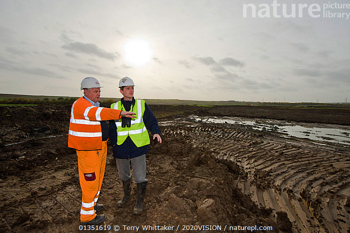 RSPB Project Manager Dave Hedges and machine operator Alan Deval. Wetland habitat ecosytem creation for the RSPB by Breheny Civil Engineers at Bowers Marsh RSPB Reserve, Thames Estuary, Essex, UK. November 2011.   Model released  ,  2020VISION,COASTS,CONSERVATION,ENGLAND,ENVIRONMENTAL,EUROPE,GREATER THAMES FUTURESCAPES,HABITAT,HABITAT CREATION,LANDSCAPES,MAN,MEN,MUD,MUDDY,PEOPLE,RESERVE,TWH_021110_0117,TWO,UK,URBAN,WETLANDS,WORKING,United Kingdom  ,  Terry Whittaker / 2020VISION