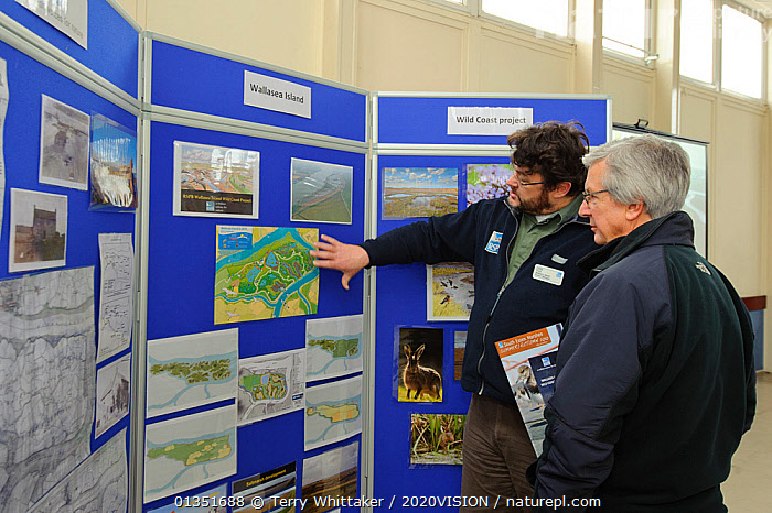 An event to introduce the local community to the RSPB Wallasea Wild Coast Project. Project manager, Chris Tyas, explains the project to a visitor and the plans for the future of Wallasea Island, Essex, UK, January 2011, Model released  ,  2020VISION,COASTS,CONSERVATION,EDUCATION,ENGLAND,EUROPE,INDOORS,MEN,PEOPLE,RESERVE,RSPB,SIGNS,TWH_300111_0008,TWO,UK,URBAN,WETLANDS,United Kingdom  ,  Terry Whittaker / 2020VISION