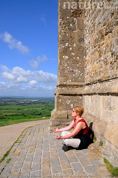 Woman meditating by the 15th century church St. Michael's Tower at the summit of Glastonbury Tor, Somerset, England, May. Model released  ,  BUILDINGS,ENGLAND,EUROPE,LANDSCAPES,MEDITATION,OUTDOORS,PEOPLE,RELAXING,SOMERSET,SPIRITUAL,TOURISM,UK,VERTICAL,United Kingdom  ,  Gary K. Smith