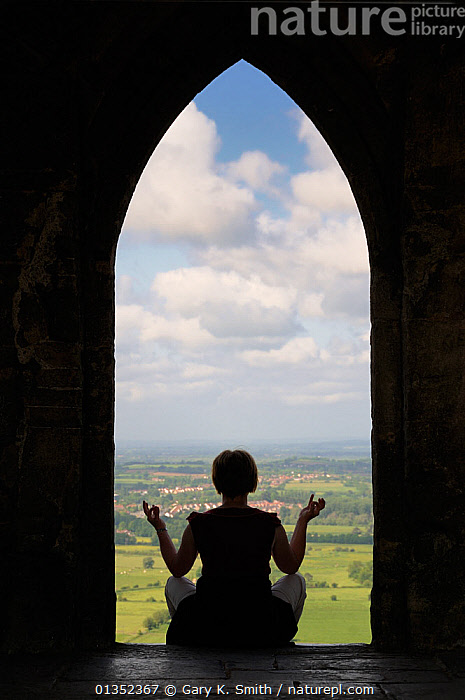 Woman meditating by the 15th century church St. Michael's Tower at the summit of Glastonbury Tor, Somerset, England, May. Model released  ,  CHURCHES,COUNTRYSIDE,ENGLAND,EUROPE,INDOORS,LANDSCAPES,MEDITATION,PEOPLE,SILHOUETTES,SPIRITUAL,TOURISM,UK,VERTICAL,United Kingdom  ,  Gary K. Smith