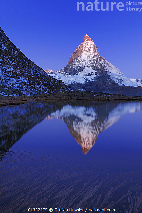 Matterhorn at sunrise in autumn with reflection in the Riffelsee. Zermatt, Valais, Switzerland, Europe, October 2008.  ,  ALPINE,AUTUMN,beauty in nature,blue sky,CALM,catalogue4,DRAMATIC,EUROPE,GEOLOGY,LAKES,LANDSCAPES,Matterhorn,MOUNTAINS,nature,Nobody,PEACEFUL,Physical Geography,reflection,REFLECTIONS,Riffelsee,Scenic,SNOW,snow capped,snowcapped,SUNRISE,Switzerland,travel destination,Valais,VERTICAL,WATER,water surface,Zermatt,CONCEPTS  ,  Stefan Huwiler